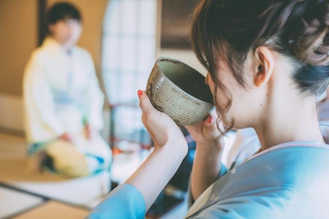 抹茶碗でお茶を飲む女性の画像