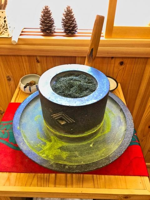 石うすで茶葉を引いている画像