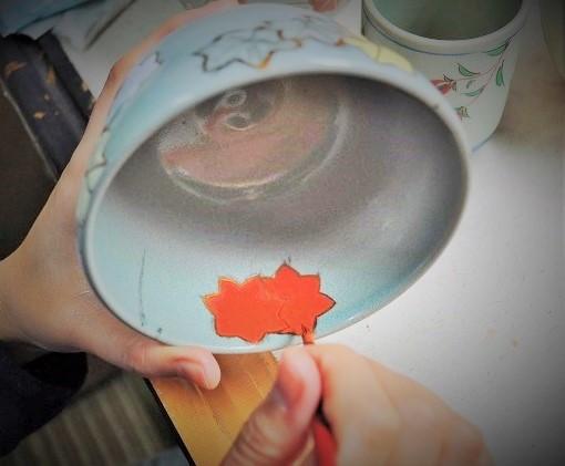 抹茶碗の内側に職人が絵付けする画像