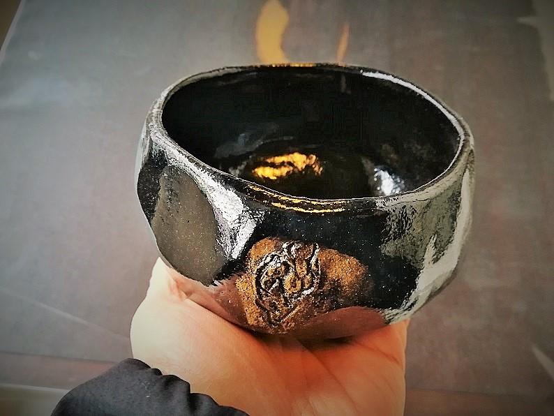 黒楽茶碗楽入を手に持つ画像