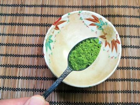 薄茶の茶葉とスプーンの画像
