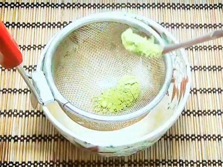 薄茶の茶葉を茶こしでコシている画像