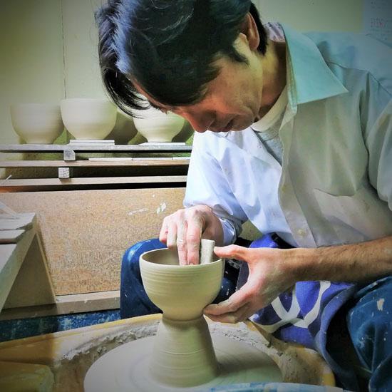職人がロクロで茶碗を成形する画像