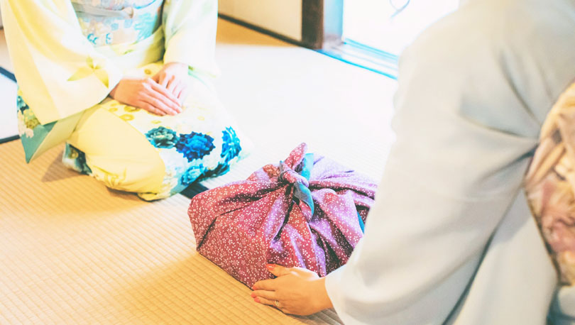 着物の女性が風呂敷に包まれた「贈りもの」を贈る画像