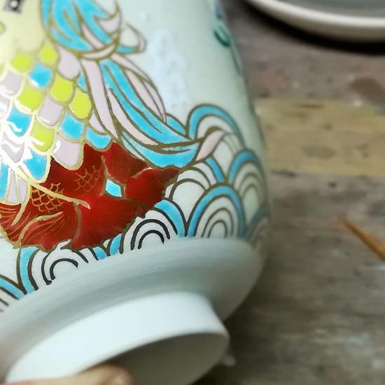 抹茶碗あまびえの足ヒレの金描きをしている画像