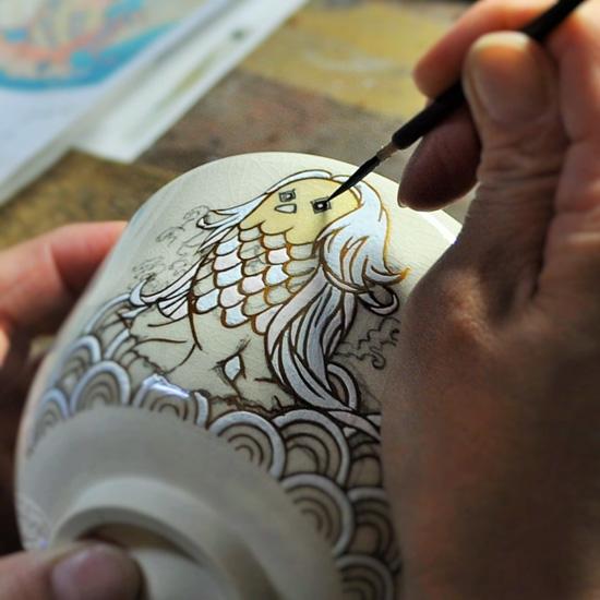 抹茶碗あまびえの顔を絵付けしている画像